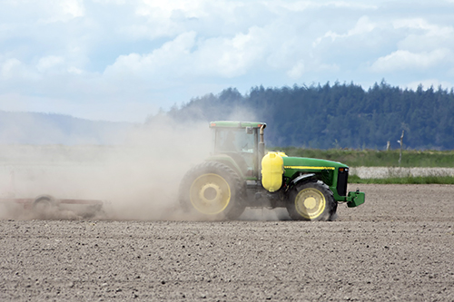 a tractor in a bare field surrounded by a cloud of dust