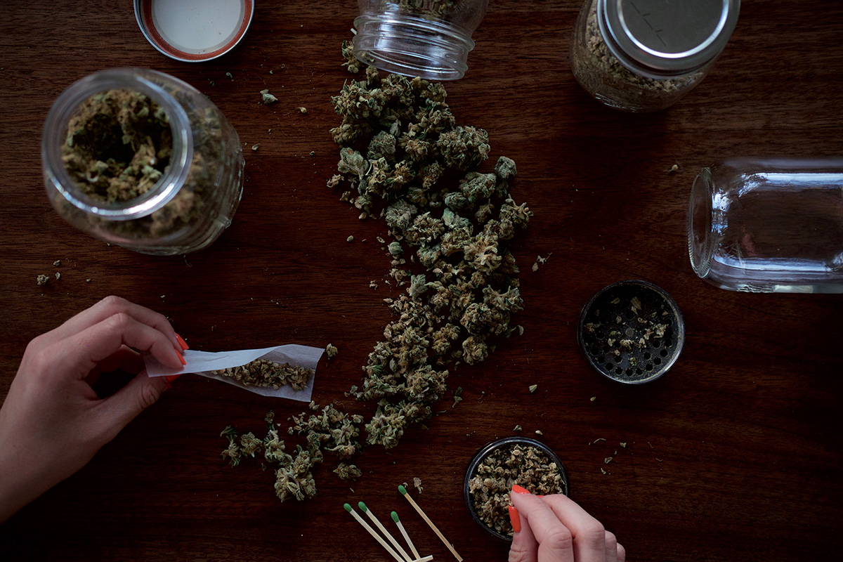 top view of wooden table with cannabis products on top and a woman's hand rolling a joint
