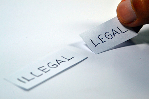 close-up of finger choosing a piece of paper with the word legal written on it over the alternative piece of paper with illegal written on it