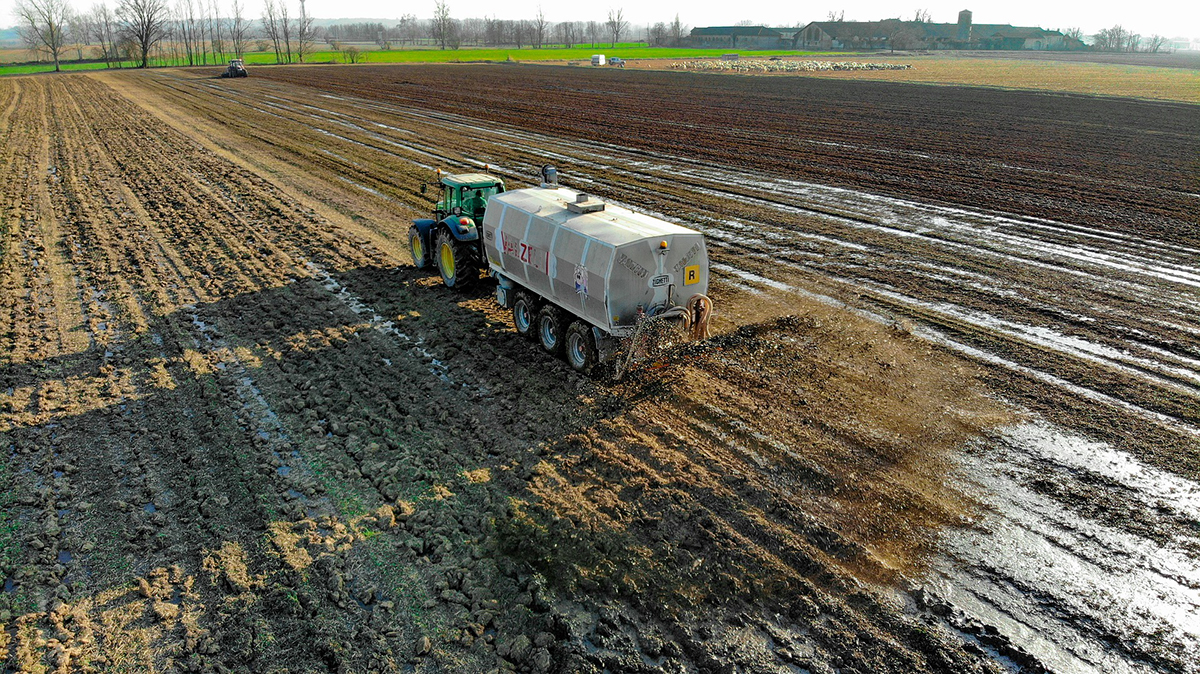 Large Truck Throwing Out Fertilizer on a muddy crop soil