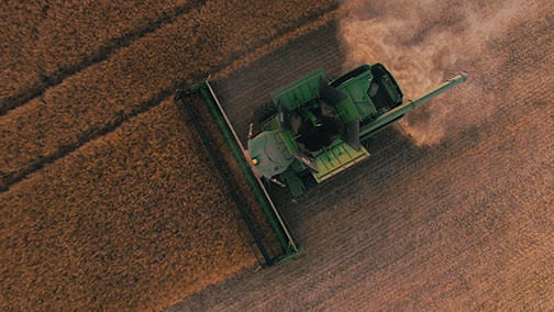a machine harvester illustrating that unsustainable agricultural practices, such as over-working the land, were one of the main causes of the dust bowl