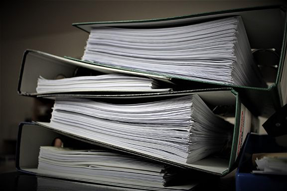 thick stacks of paper in books highlighting that there are over 700 cannabis license applications awaiting approval in Canada