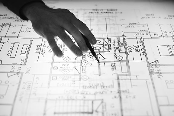 hand holding pen over a black and white blueprint, highlighting new regulations for micro-license facilities