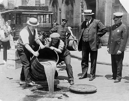 black and white photo of agents pouring out liquor into a sewer during a Prohibition raid while police officers watch